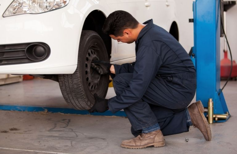 Image of an auto mechanic tending to a car's tire